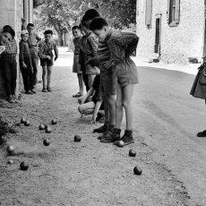 La petite fille regarde les garçons jouer à la pétanque