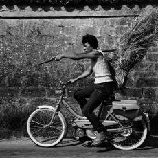 A vélomoteur, la jeune agricultrice transporte une botte de paille