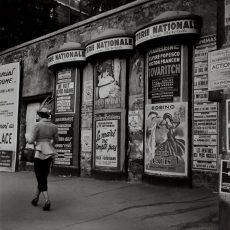 Habillée d'un tailleur trotteur, passant devant les colonnes Morris du quartier de l'Opéra, une femme chic