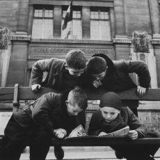Quatre jeunes garçons lisant le «Journal de Mickey», devant une école communale de garçons