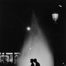 De nuit, un couple passe devant les fontaines illuminées du rond-point des Champs-Élysées