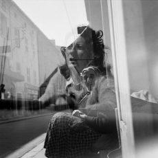 Vieille femme dans la rue. Reflets jeune femme dans une vitrine
